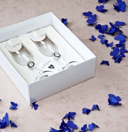 Couple of Wedding Bride and Groom Champagne Glasses in a Paper Box with Purple Butterflies on Beige Background photo