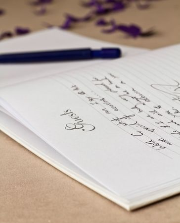 wedding guest: Opened wedding guest book with writing and a pen on a beige background