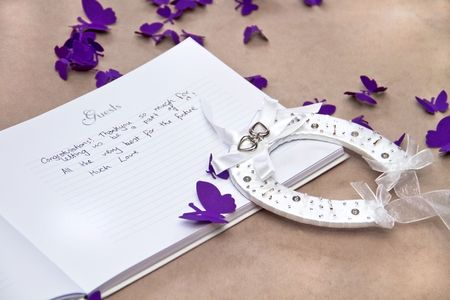 Opened Wedding Guest Book with a Good Luck Horseshoe and Purple Butterflies on Beige Background