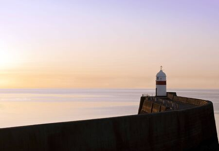 Peacefull scenery of Lighthouse with a breakwater wall and calm sea during sunrise on the Isle of Man photo