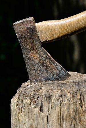 gash: Closeup on Lumberjacks axe stuck in a chopping block with natural background
