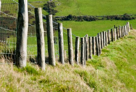 pasture fence: Wodded post with Metal Wire Fence Running through a Grass Field for Cattle Stock Photo