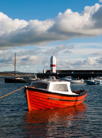 Small Fishing Boat docked in a harbour with Lighthouse and Cloudy sky in the background photo