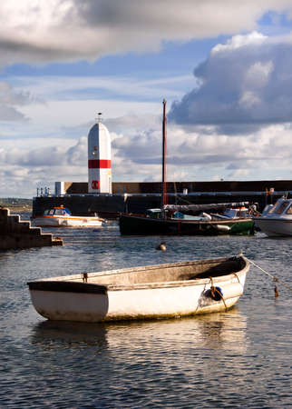 tied in: Small Boat tied in a harbour with Lighthouse and Cloudy sky in the background Stock Photo