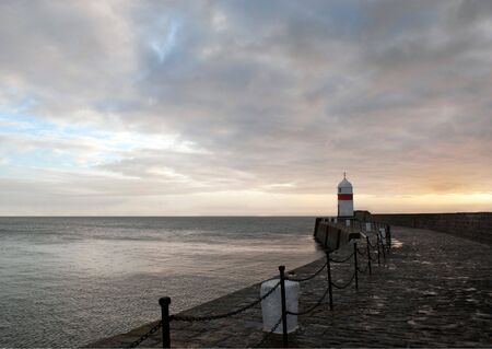 Path to Lighthouse on the Breakwater wall with Dramatic sky and Calm Sea at Dawn Stock Photo - 8180117