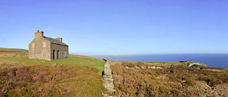 Stitched Panorama of Abandoned House - Chasms, Green Grass, Seas and Heather Field with Bright Blue Sky photo