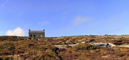 Stitched Panorama of Abandoned House in the Heather Field with Bright Blue Sky photo