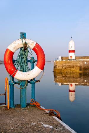 White and Red Life Buoy Wheel in a Harbour with an old Lighthouse on the Breakwater Wall in the background and Sea Water Reflection Stock Photo - 9643145