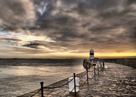 Dramatic HDR Set. Cloudy Sky and Stony Path to the Lighthouse with Sunrise over the sea Stock Photo