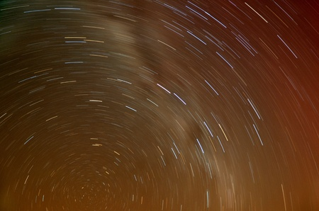 Long exposure Star Trails with yellow shine from city in the desert  photo