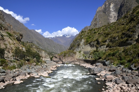 Wild Urubamba river flowing through valley with high snow capped mountains and blue sky in the background photo