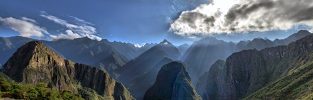View of Andes Mountain Range from Machu Picchu. Beautiful scenery with Sun Rays shining through the Mountains Peaks Stock Photo