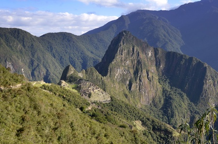 unesco world cultural heritage: View of Machu Pichu with Huayna Picchu from far, rainforest jungle and mountains with blue sky in the background