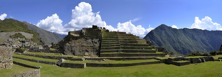 machu picchu: Panorama of Terraces with Sun Temple at Macchu Picchu Historic Site with Andes and Cloudy Sky in the Background Stock Photo