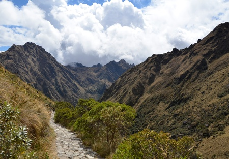 Ancient Stone Inca Trail Path in the Andes Leading to Machu Picchu With Cloudy Sky in the Background photo