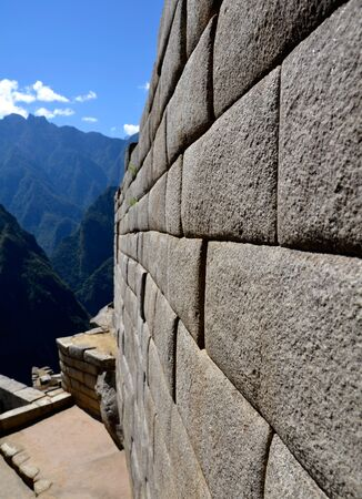 incan: Example of Incan Stone Craft - Side Wall of a Temple on Machu Picchu site with Andes in the background Stock Photo