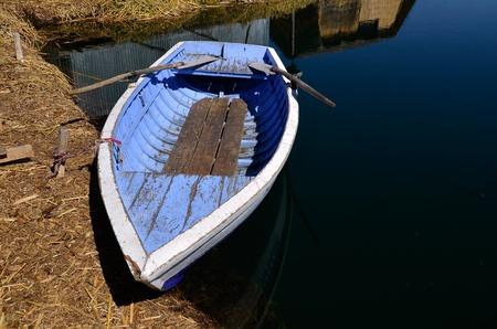 isla flotante: Barco viejo remo azul atada a la isla de los Uros en el lago navegable m�s alto del mundo - Titicaca