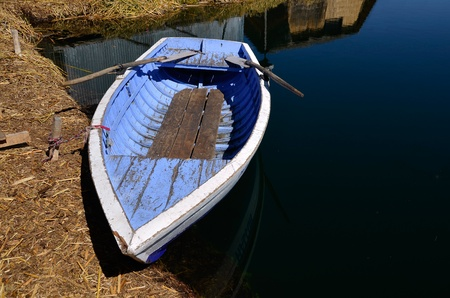 Old Blue Rowing Boat tied to Uros Floating Island on Highest navigable Lake in the World - Titicaca Stock Photo - 10988221