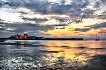 peels: Famous historic Peel Castle with Dramatic sunset sky and reflection on the beach. HDR Effect. Isle of Man