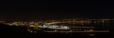 Panorama of Douglas Bay on Isle of Man with Boat in the harbour and a night sky. photo
