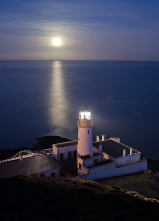 searchlight: Lighthouse with Full Moon Reflecting in the Sea on the Isle of Man - Vertical Composition