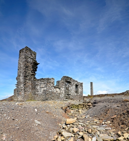 Old abandoned ruined miners cottage over bright blue sky photo