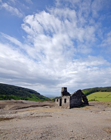 broken house: Old abandoned ruined miners cottage over cloudy blue sky and forest in the background Stock Photo