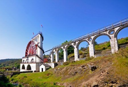 The Great Laxey Wheel with viaduct on sunny day - Isle of Man Stock Photo