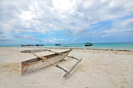 Wooden Fishing boat on a beach of Zanzibar Island with tourist boats in the background on a bright sunny day  Stock Photo - 15870619