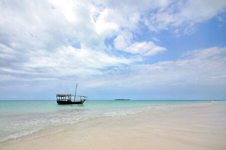 White Sandy Beach with a Wooden Tourist Boat and Island in the background with Blue Sky on a Beautiful Island of Zanzibar Stock Photo - 15870618