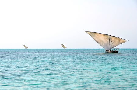 Three Traditional Fishing Boats Sailing on the Ocean with Turquoise colored Water  photo