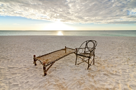 sea bed: Old Bamboo Chair and Camp Bed Sitting on Sandy Beach with Sea and Setting Sun Over Puffy Clouds.