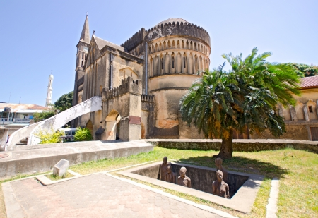 restraining: Slave Market Memorial with Church in the Background in Stone Town on Zanzibar Island - Tanzania Stock Photo