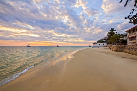Beautiful Sunset in the Stone Town on Zanzibar Island with boats sailing and sandy beach resort. Tanzania - East Africa