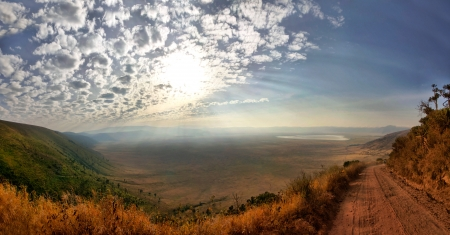 Panorama of Ngorongoro Crater with sunny blue sky with few clounds and gravel road.