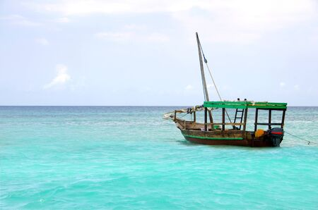 Wooden boat floating on the turquoise sea against blue sky Stock Photo - 16493974