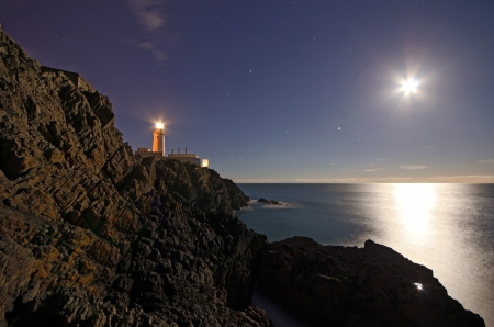 night sky and stars: Lighthouse on top of cliffs with night sky, stars and full Moon reflecting in the Sea on the Isle of Man  Stock Photo