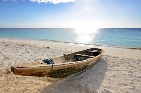 Wooden Fishing boat on a beach of Zanzibar Island with tourist boats in the background on a bright sunny day Stock Photo - 16871173
