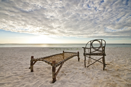 Old Bamboo Chair and Camp Bed Sitting on Sandy Beach with Sea and Setting Sun Over Dramatic Sky  photo