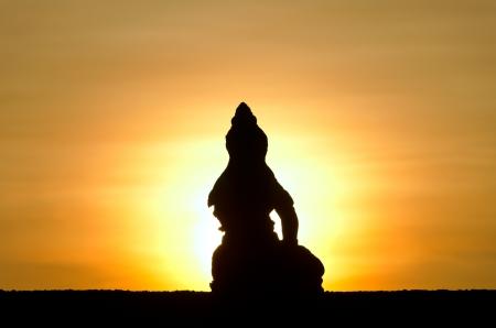 budha: Silhouette of sitting Buddha against rising sun and orange sky