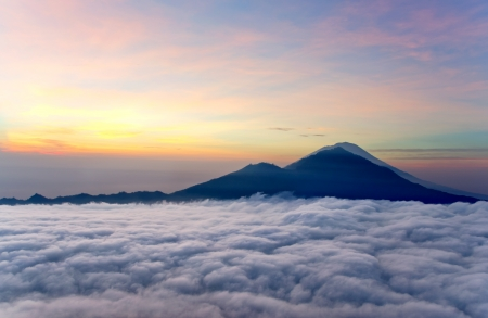 Sunrise above clouds with a mountain volcano view  Mt  Batur Bali Indonesia photo