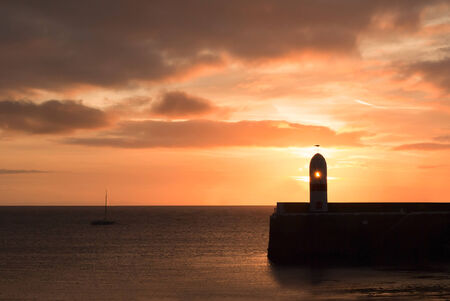 Silhouette of Lighthouse on breakwater wall with calm sea during sunrise.  Tranquil scene on Isle of Man photo