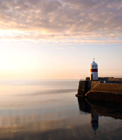 Lighthouse on breakwater wall with calm sea during sunrise.  Tranquil scene on Isle of Man photo