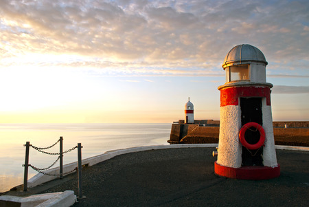 Lighthouses on breakwater wall with calm sea during sunrise.  Tranquil scene on Isle of Man