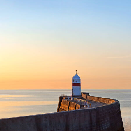 peacefull: Lighthouse on breakwater wall with calm sea during sunrise.  Tranquil scene on Isle of Man