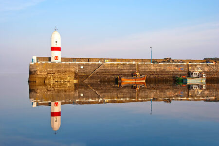 Old Lighthouse on Breakwater Wall in a Harbour with Boat. Sea and Bright Blue sky with clear Water Reflection. Isle of Man photo