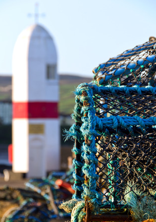 lobster boat: Crab nets closeup with Lighthouse in background.