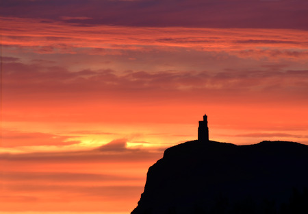 Vivid Sunset colours with silhouette of Milner Tower on Brada Head, Isle of Man, UK photo
