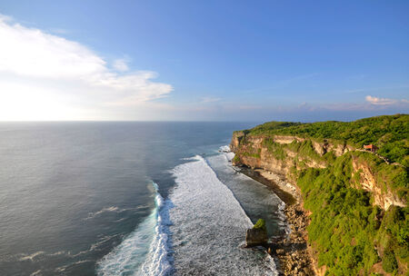 kecak: Big cliffs with perfect waves on a sunny day at Uluwatu, Bali Indonesia