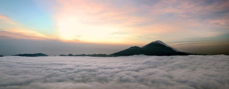 Panorama of Sunrise above clouds with a mountain volcano view. Mt. Batur Bali Indonesia photo